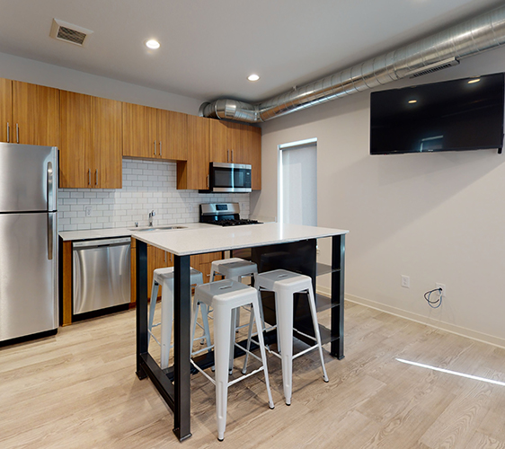 Kitchen with movable island and swivel mounted TV
